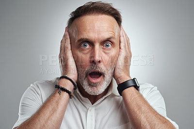 Buy stock photo Studio portrait of a mature man covering his ears and looking shocked against a grey background