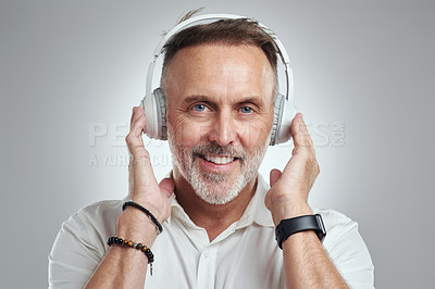 Buy stock photo Studio portrait of a mature man wearing headphones against a grey background