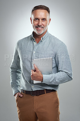 Buy stock photo Studio portrait of a mature man holding a digital tablet against a grey background
