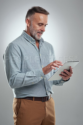 Buy stock photo Studio shot of a mature man using a digital tablet against a grey background