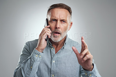 Buy stock photo Studio shot of a mature man looking confused while talking on a cellphone against a grey background
