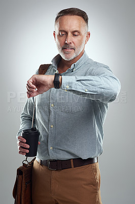 Buy stock photo Studio shot of a mature man carrying a bag and cup of coffee while the time on his wristwatch against a grey background