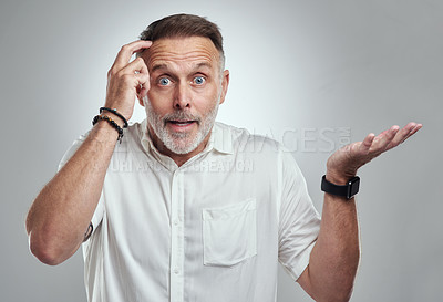 Buy stock photo Studio portrait of a mature man looking confused against a grey background
