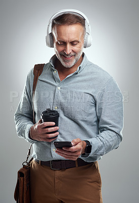 Buy stock photo Studio shot of a mature man wearing headphones and using a cellphone while carrying a bag and cup of coffee against a grey background