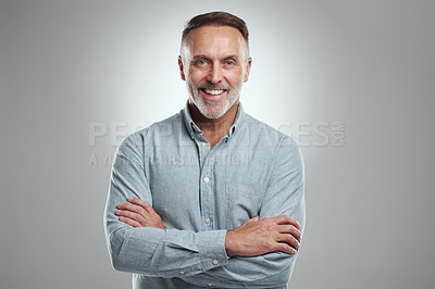Buy stock photo Studio portrait of a mature man standing with his arms folded against a grey background