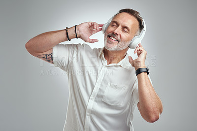 Buy stock photo Studio shot of a mature man wearing headphones against a grey background