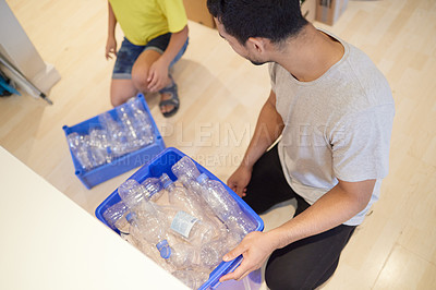 Buy stock photo Shot of a young man of and his child  gathering bottles to recycle at home