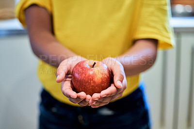 Buy stock photo Cropped shot of a boy holding an apple in his hands at home