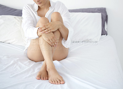 Buy stock photo Cropped shot of an unrecognizable young woman showing off her silky soft legs while sitting on her bed at home