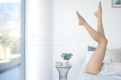 Buy stock photo Cropped shot of an unrecognizable young woman showing off her silky soft legs while lying on her bed at home