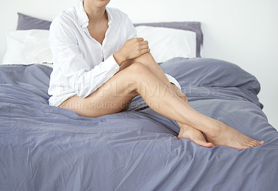 Buy stock photo Cropped shot of an unrecognizable young woman rubbing her silky soft legs while sitting on her bed at home