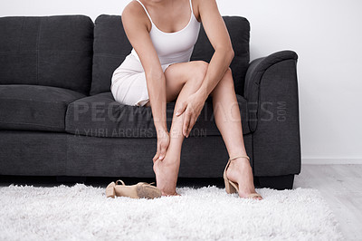 Buy stock photo Shot of a woman rubbing her feet after wearing heels