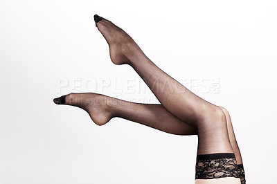 Buy stock photo Cropped shot of an unrecognizable woman wearing a pair of black stockings in the studio