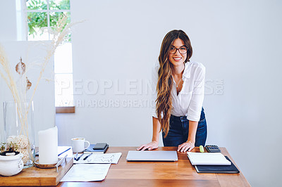 Buy stock photo Shot of an attractive young businesswoman standing alone by her desk in her home office