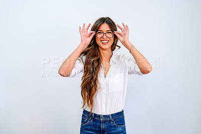 Buy stock photo Shot of an attractive young businesswoman standing alone against a white wall and holding her glasses
