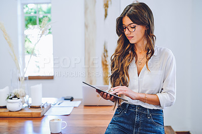 Buy stock photo Shot of an attractive young businesswoman sitting alone on her desk in her home office and using a digital tablet