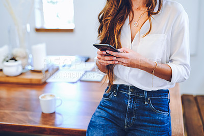 Buy stock photo Cropped shot of an unrecognizable businesswoman sitting alone on her desk in her home office and using her cellphone