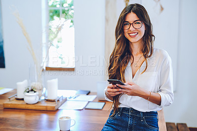 Buy stock photo Shot of an attractive young businesswoman sitting alone on her desk in her home office and using her cellphone