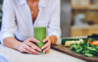 Buy stock photo Shot of an unrecognisable woman making a healthy smoothie at home