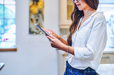 Buy stock photo Shot of an unrecognisable woman using a digital tablet at home
