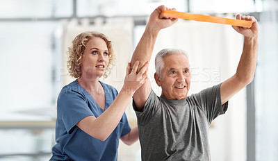 Buy stock photo Shot of a female nurse helping her elderly patient with physical therapy using a resistance band