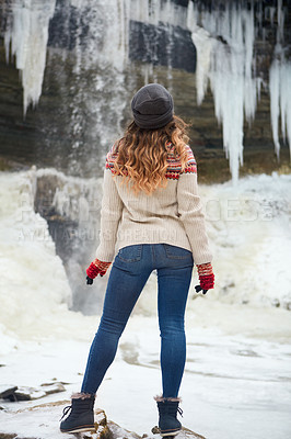 Buy stock photo Rearview shot of an unrecognizable young woman spending the day outside during winter