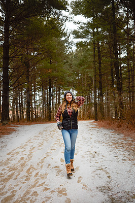 Buy stock photo Shot of a young woman hiking in the wilderness during winter