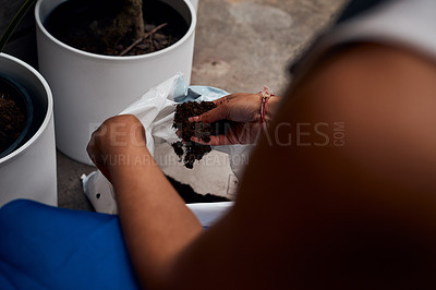 Buy stock photo Shot of an unrecognisable woman holding soil while working in a garden centre