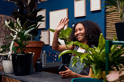 Buy stock photo Shot of a young woman standing behind the counter of a garden centre and waving