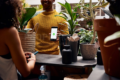 Buy stock photo Shot of an unrecognizable man using a smartphone to pay for plants at a garden centre