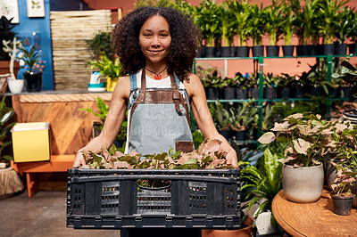 Buy stock photo Portrait of a young woman holding a crate of plants while working in a garden centre