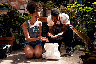 Buy stock photo Shot of a young man and woman working with soil in a garden centre