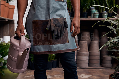 Buy stock photo Shot of an unrecognisable man holding a watering can while working in a garden centre