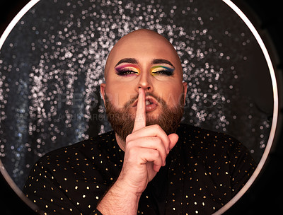 Buy stock photo Shot of a young man wearing theatrical makeup and placing his fingers on his lips in a studio