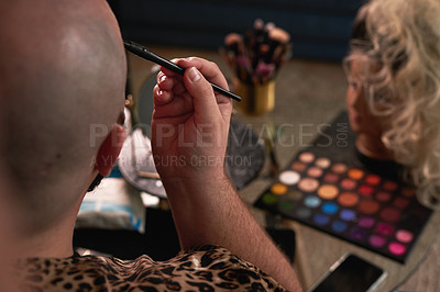 Buy stock photo Shot of an unrecognisable man applying theatrical makeup in a studio
