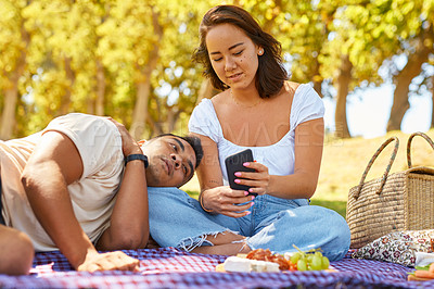 Buy stock photo Shot of a woman showing her boyfriend something on her cellphone while on a picnic at the park