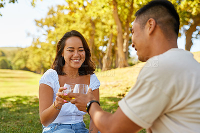 Buy stock photo 4k video footage of a young couple sharing a toast while on a picnic