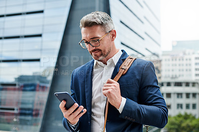 Buy stock photo Shot of a mature businessman using a cellphone in the city