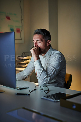 Buy stock photo Shot of a mature businessman yawning while working on a computer in an office at night
