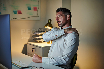 Buy stock photo Shot of a mature businessman experiencing shoulder pain while working on a computer in an office at night