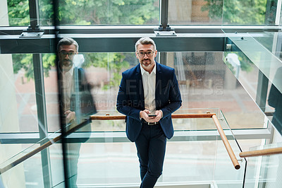 Buy stock photo Portrait of a mature businessman using a cellphone while standing on a staircase in an office
