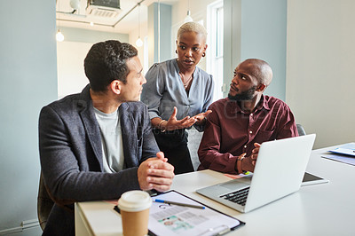 Buy stock photo Shot of a group of businesspeople having a discussion while working on a laptop in an office