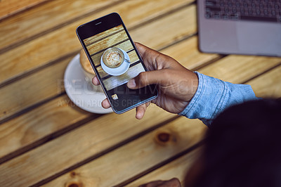 Buy stock photo Cropped shot of an unrecognizable man sitting in a cafe and photographing his coffee with his cellphone