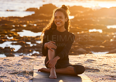 Buy stock photo Shot of an attractive young woman sitting on her yoga mat during a yoga session on the beach at sunset