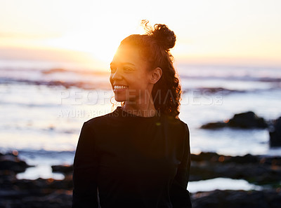 Buy stock photo Shot of an attractive young woman standing alone after doing yoga on the beach at sunset