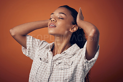 Buy stock photo Shot of a woman stroking her wet hair against an orange background