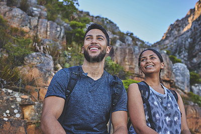 Buy stock photo Shot of a young couple enjoying the sunset view while out on a hike on a mountain range