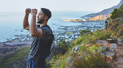 Buy stock photo Shot of a young man celebrating the completion of his hike at the top of the mountain
