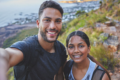 Buy stock photo Shot of a young couple taking photos while out on a hike in a mountain range outside