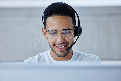 Buy stock photo Shot of a young businessman working at his desk in his office